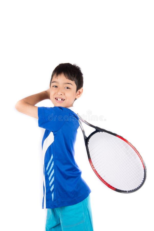 Kleiner Junge, der in der Hand Tennisschläger und -Tennisball spielt lizenzfreie stockbilder
