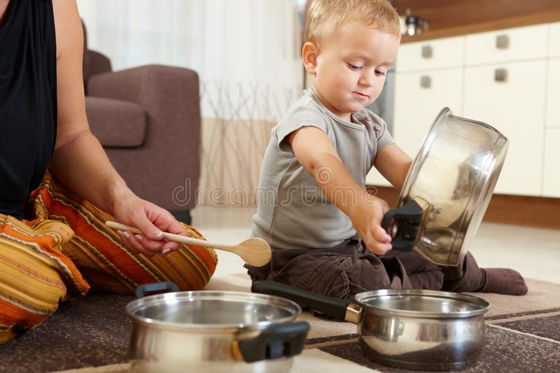 Kleiner Junge, der in der Küche spielt lizenzfreie stockfotografie