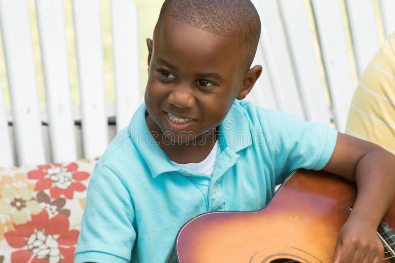 Kleiner Junge, der die Gitarre spielt lizenzfreies stockfoto