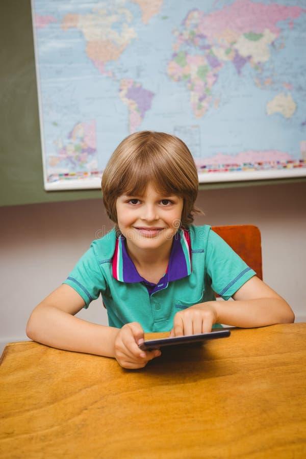 Kleiner Junge, der digitale Tablette im Klassenzimmer verwendet lizenzfreie stockfotografie