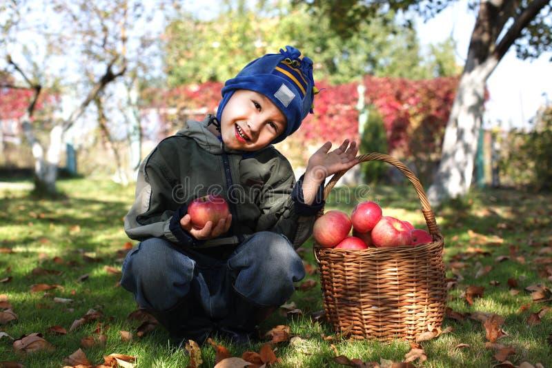 Kleiner Junge, der draußen mit Äpfeln aufwirft stockbild