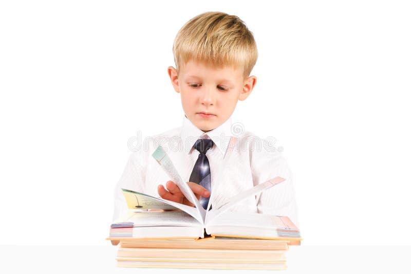 Kleiner Junge, der ein Buch getrennt über Weiß liest lizenzfreie stockbilder
