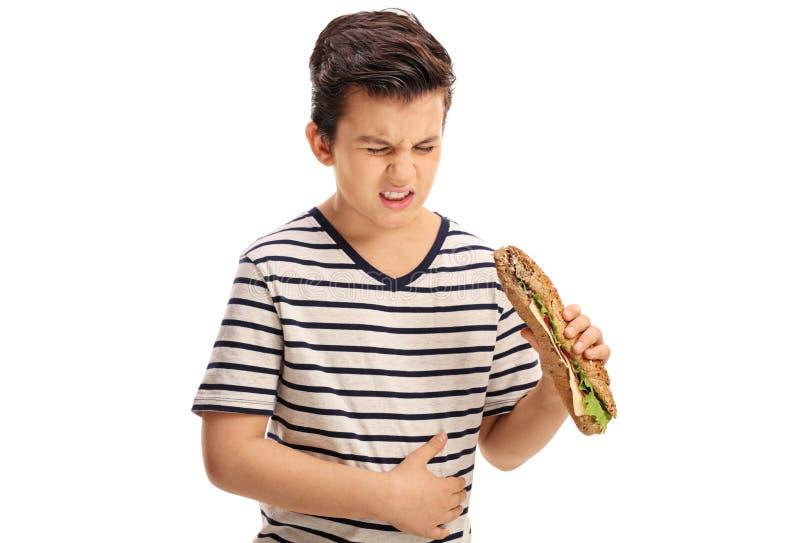 Kleiner Junge, der ein Sandwich isst und Magenschmerzen erfährt stockfotos