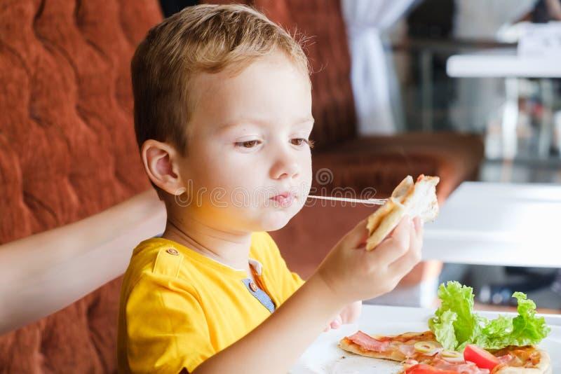 Kleiner Junge, der eine kleine Pizza isst lizenzfreies stockfoto