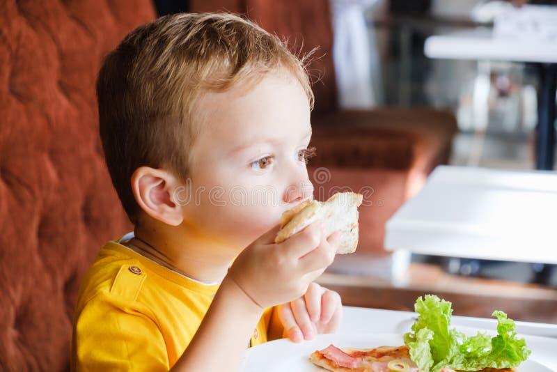 Kleiner Junge, der eine kleine Pizza isst lizenzfreie stockfotografie