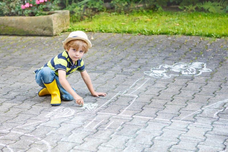 Kleiner Junge, der eine Zugmaschine mit Kreide im Sommer malt lizenzfreies stockbild