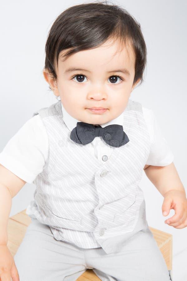 Kleiner Junge, der in einem glücklichen Kind des weißen Hemdes mit Fliege lächelt stockfotografie