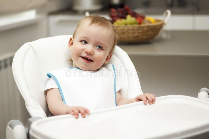 Kleiner Junge, der in einem Hochstuhl und in einem Lachen sitzt stockfoto