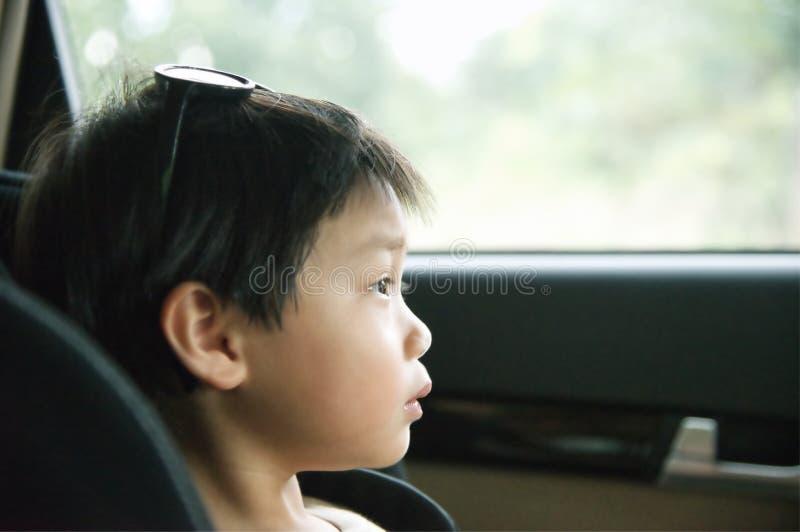 Kleiner Junge, der in einem Kindersitz im Auto sitzt und Fenster betrachtet: Nahaufnahme stockbilder
