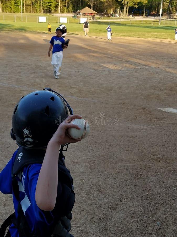 Kleiner Junge, der einen Baseball wirft stockfotografie