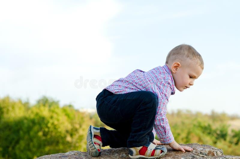 Kleiner Junge, der einen Felsen steigend erforscht stockbild
