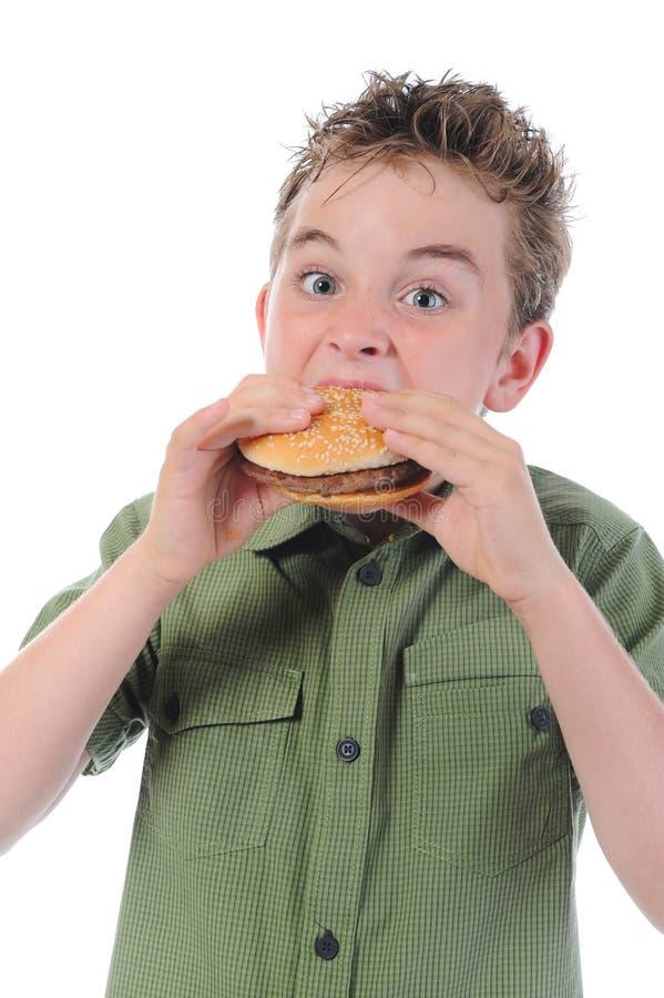 Kleiner Junge, der einen Hamburger isst lizenzfreie stockfotos