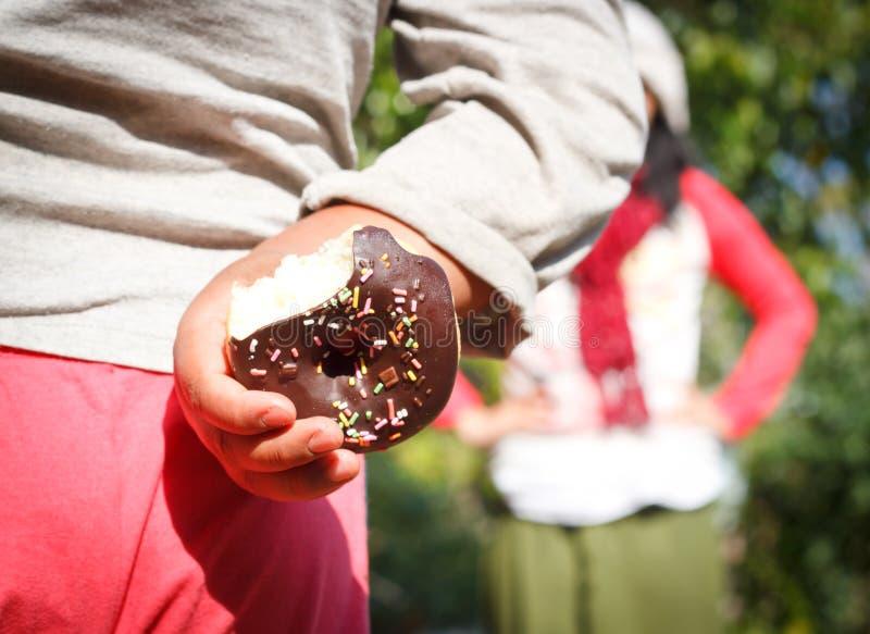 kleiner Junge, der einen Schokoladendonut versteckt stockbilder