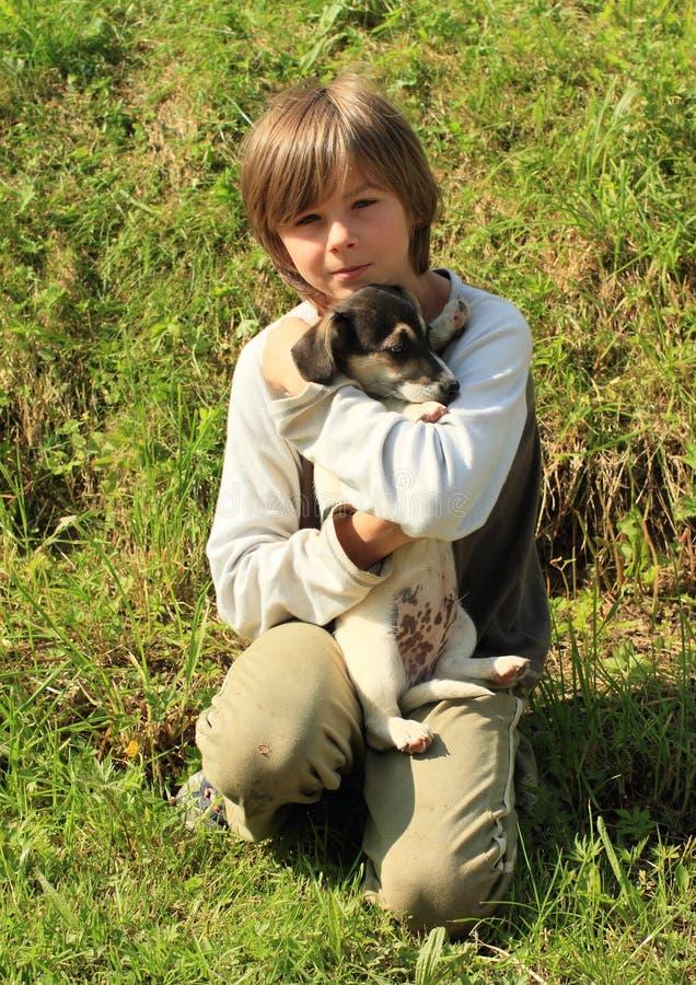 Kleiner Junge, der einen Welpen hält lizenzfreies stockbild