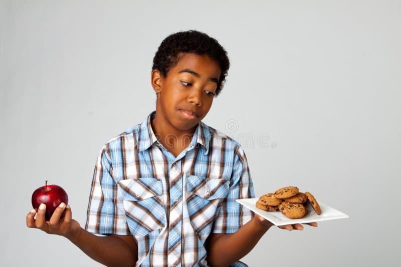Kleiner Junge, der Entscheidungen vom Essen von gesunden Versen ungesund trifft stockbilder