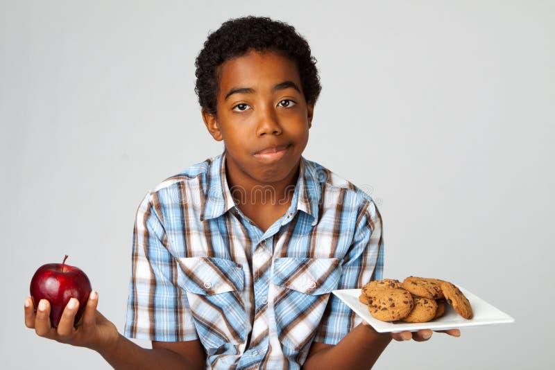 Kleiner Junge, der Entscheidungen vom Essen von gesunden Versen ungesund trifft lizenzfreies stockfoto