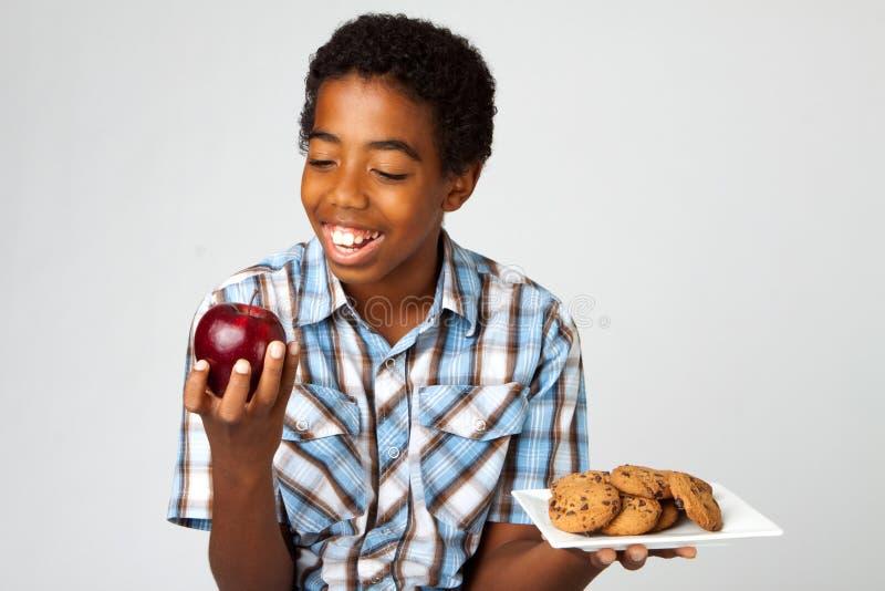 Kleiner Junge, der Entscheidungen vom Essen von gesunden Versen ungesund trifft stockfotos