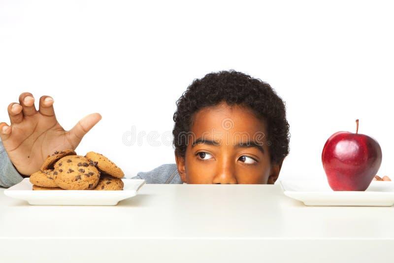 Kleiner Junge, der Entscheidungen vom Essen von gesunden Versen ungesund trifft lizenzfreie stockbilder