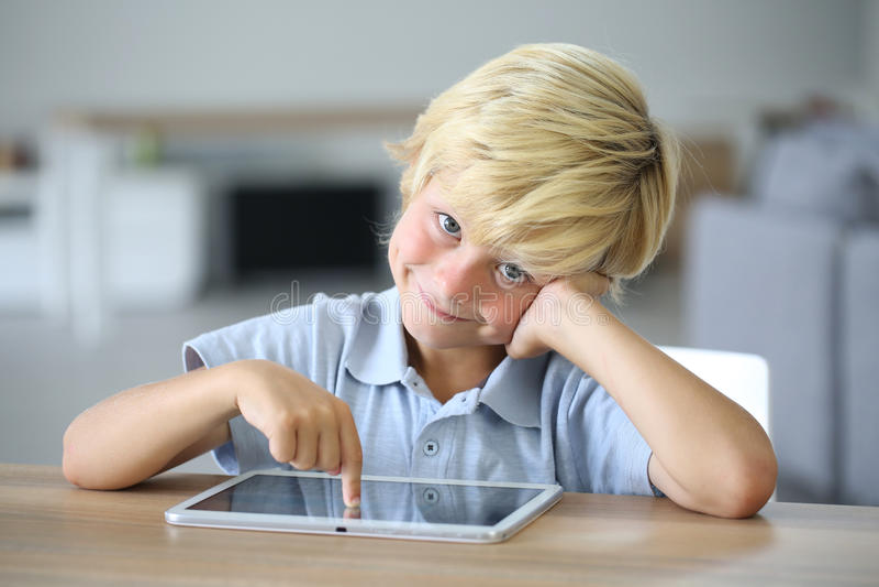 Kleiner Junge, der Finger auf Tablette zeigt lizenzfreie stockfotos