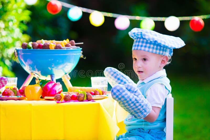 Kleiner Junge an der Gartengrillpartei lizenzfreie stockfotografie