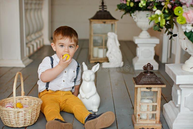 Kleiner Junge in der gelben Hose sitzt auf dem Boden im Innenraum stockfotos