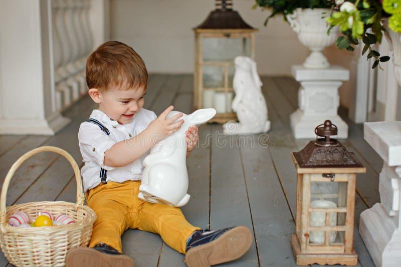 Kleiner Junge in der gelben Hose sitzt auf dem Boden im Innenraum stockfoto