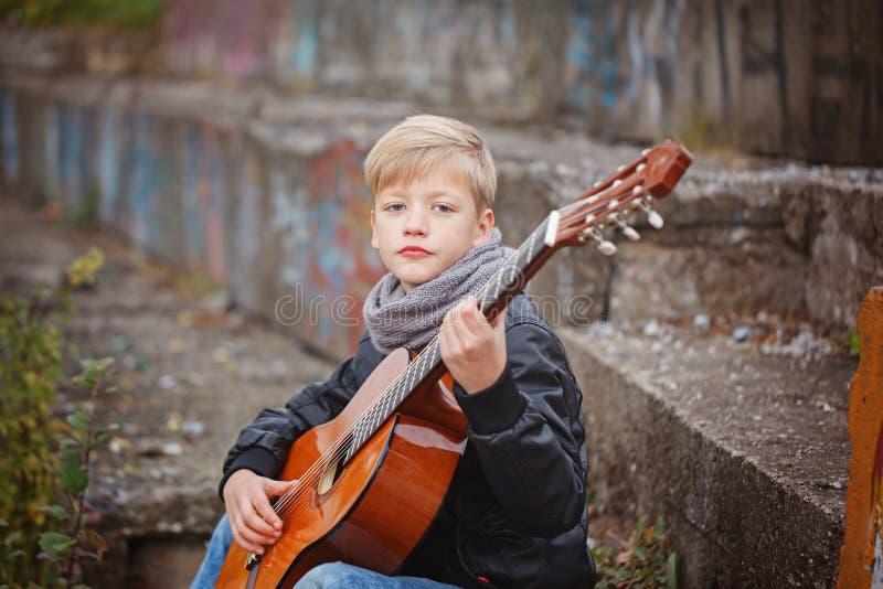 Kleiner Junge, der Gitarre am Herbstkältetag spielt Children& x27; s-intere stockbilder