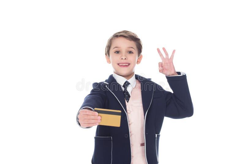 kleiner Junge, der goldene Kreditkarte und okayzeichen hält, stockfotos