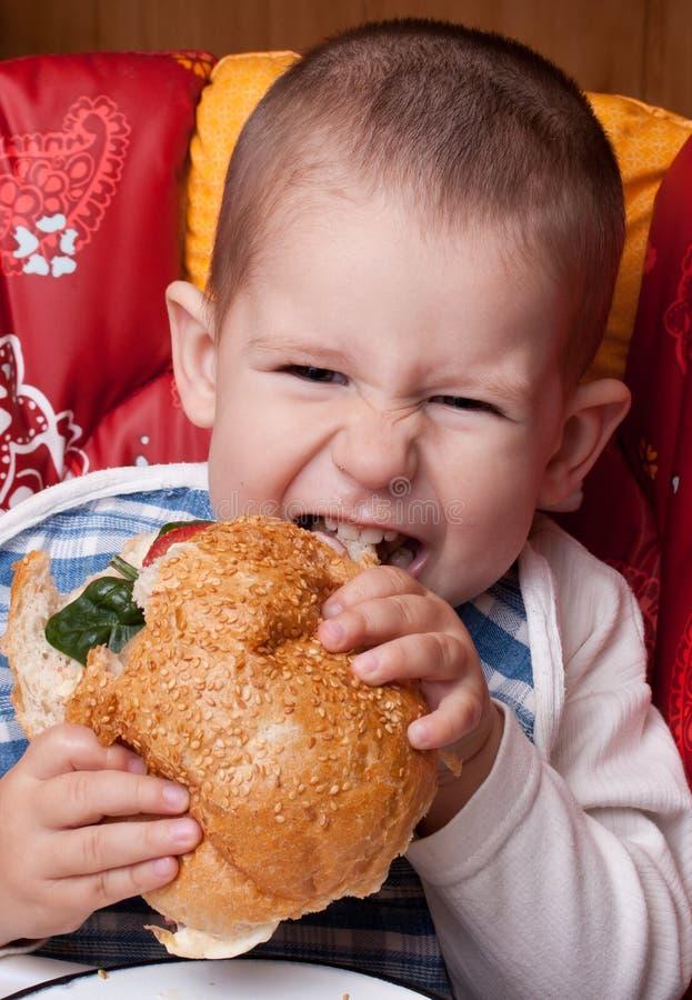 Kleiner Junge, der Hamburger isst lizenzfreie stockfotos
