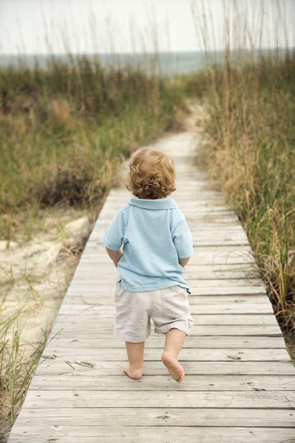 Kleiner Junge, der hinunter Strandgehweg geht. lizenzfreie stockfotografie