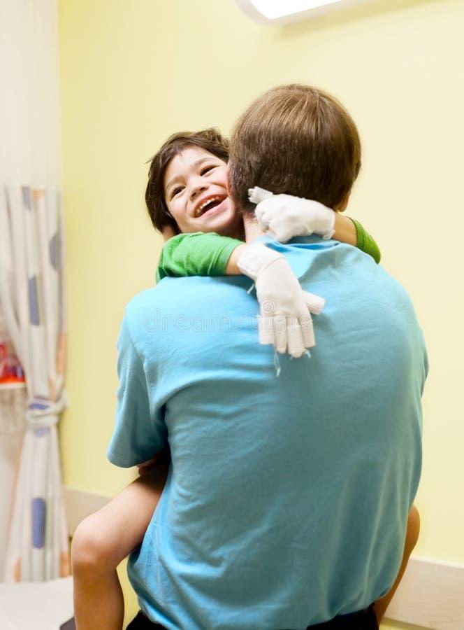 Kleiner Junge, der im Büro des Doktors, lachend sitzt lizenzfreie stockbilder