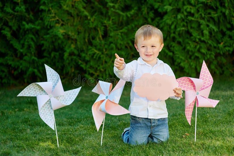 Kleiner Junge, der im Park auf dem Gras mit Windmühlen spielt stockfotografie