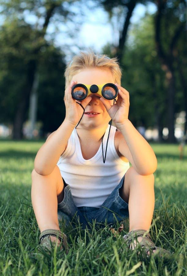 Kleiner Junge, der im Park mit Binokel sitzt stockbild