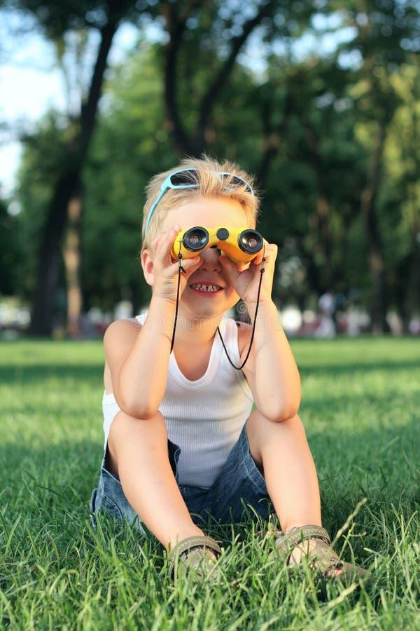 Kleiner Junge, der im Park mit Ferngläser sitzt lizenzfreies stockbild