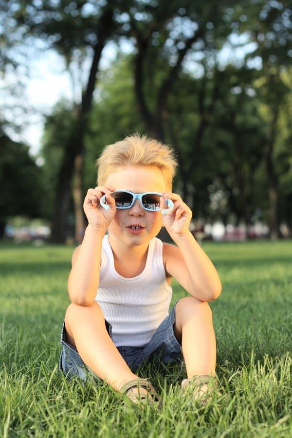 Kleiner Junge, der im Park sitzt stockfoto