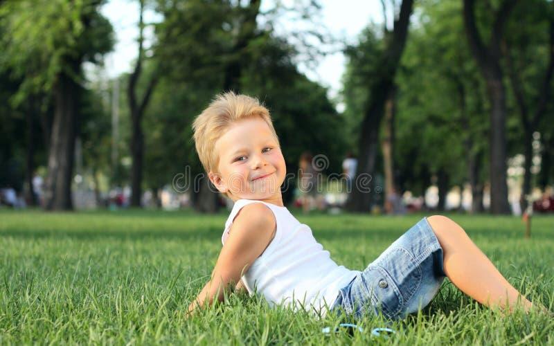 Kleiner Junge, der im Park sitzt lizenzfreie stockfotos