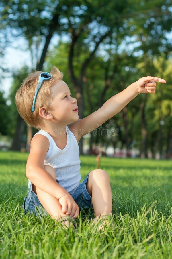 Kleiner Junge, der im Park sitzt stockbild
