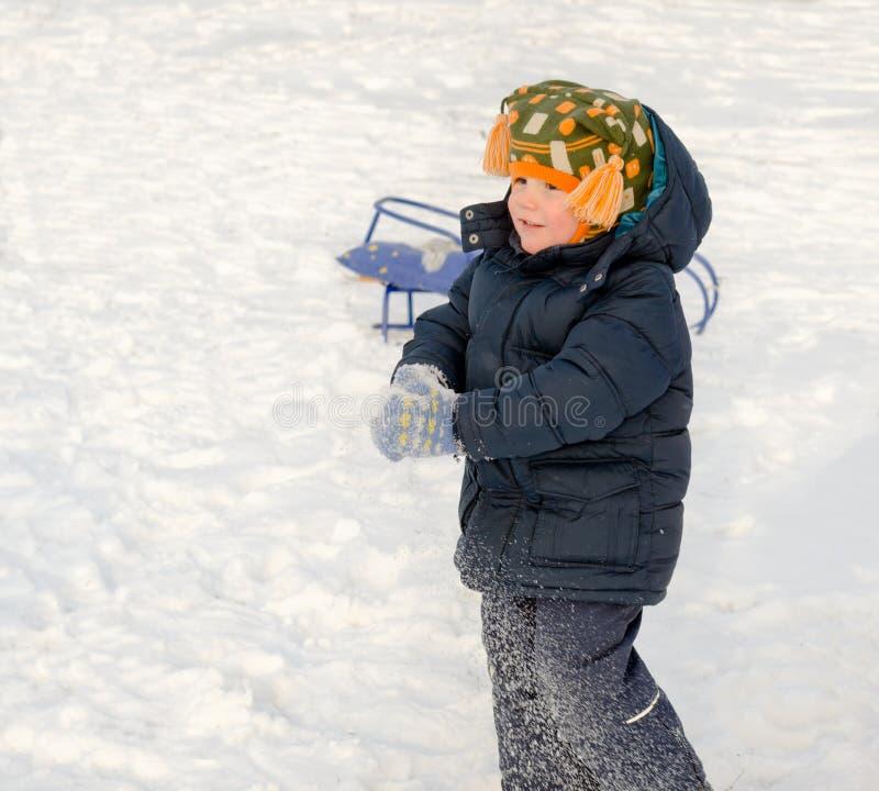 Kleiner Junge, der im Schnee spielt lizenzfreie stockbilder