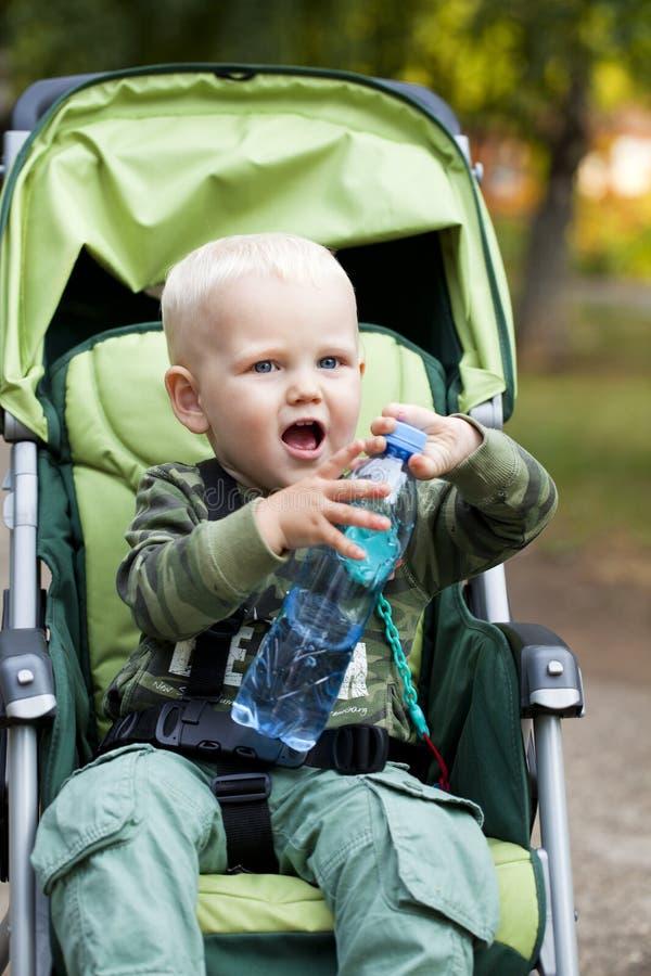 Kleiner Junge, der im Spaziergänger sitzt lizenzfreies stockfoto