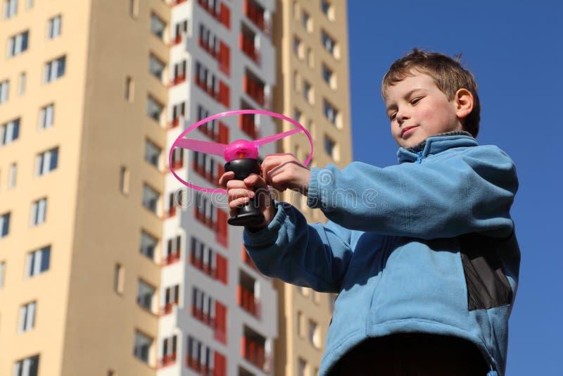 Kleiner Junge in der Jacke spielt mit rosafarbenem Propeller lizenzfreie stockfotos