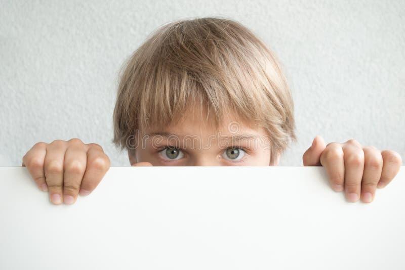 Kleiner Junge, der leeres weißes Zeichen halten oder Plakat, das sein Gesicht versteckt lizenzfreie stockfotos