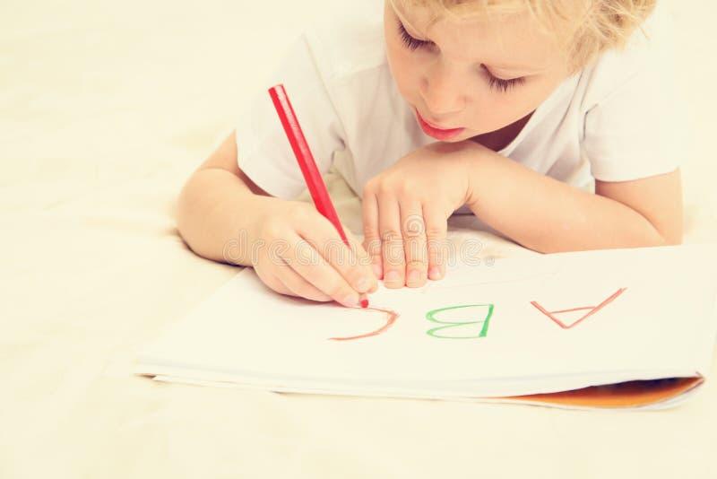 Kleiner Junge, der lernt, Briefe zu schreiben stockbild