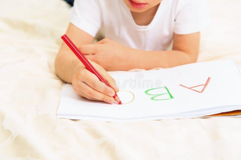 Kleiner Junge, der lernt, Briefe zu schreiben lizenzfreies stockbild