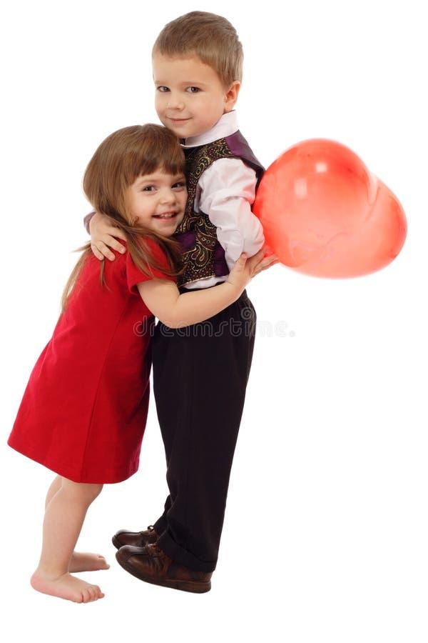 Kleiner Junge, der Mädchen mit rotem Ballon umarmt lizenzfreie stockfotografie