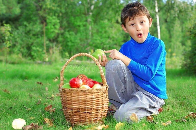 Kleiner Junge, der mit Äpfeln aufwirft stockfoto