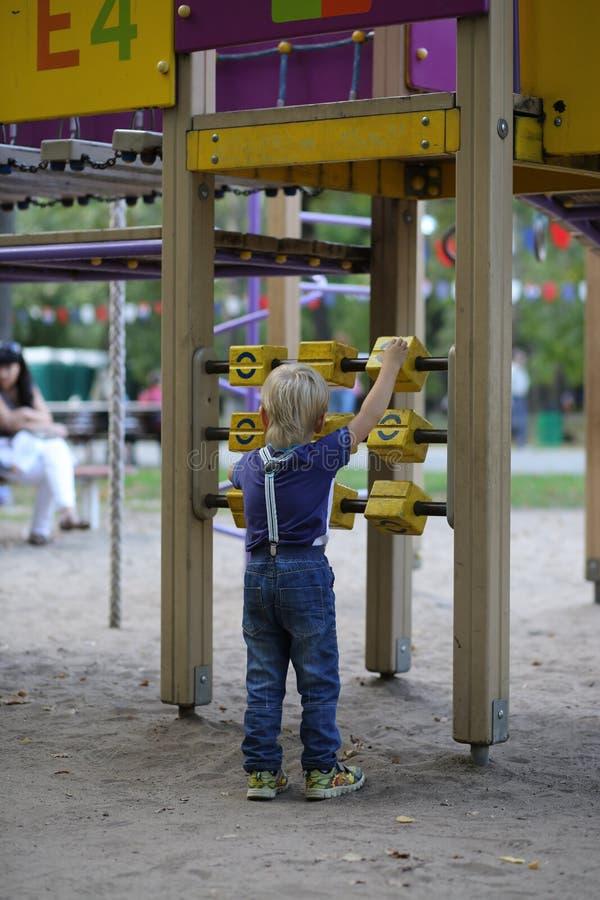 Kleiner Junge, der mit Blöcken auf dem Spielplatz spielt lizenzfreie stockbilder