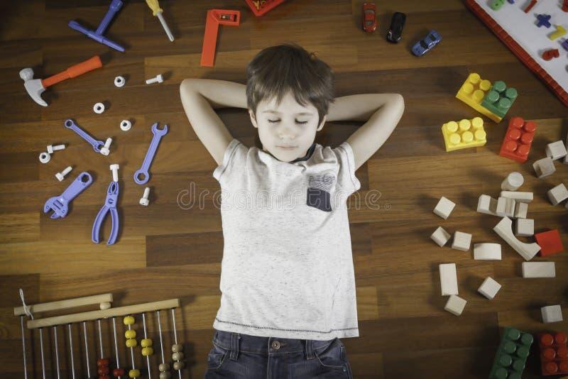 Kleiner Junge, der mit den Händen hinter den Haupt- und geschlossenen Augen auf dem Bretterboden und vielen bunten Spielwaren um  lizenzfreie stockbilder