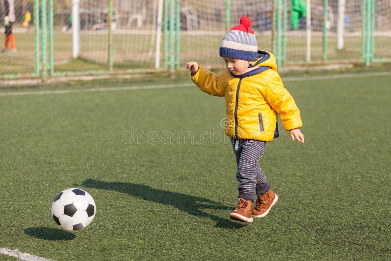 Kleiner Junge, der mit Fußball- oder Fußballball spielt Sport für Übung und Tätigkeit lizenzfreies stockfoto