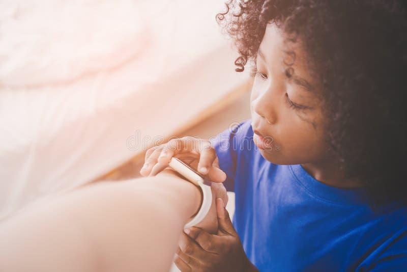 Kleiner Junge, der mit intelligenter Uhr auf einem Mannhandgelenk spielt lizenzfreies stockbild