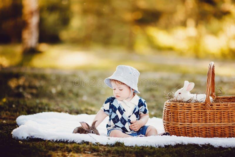 Kleiner Junge, der mit Kaninchen spielt lizenzfreie stockfotografie